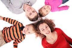 Vierköpfige Familie, die auf Fußboden liegt lizenzfreies stockbild