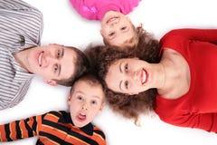 Vierköpfige Familie, die auf Fußboden liegt lizenzfreie stockfotos