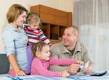Vierköpfige Familie, die Budget plant lizenzfreie stockbilder