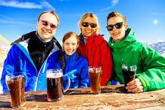 Vierköpfige Familie, die ein Getränk in den Alpen genießt Lizenzfreies Stockbild