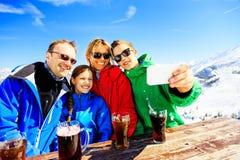 Vierköpfige Familie, die ein Getränk in den Alpen genießt Stockfotos