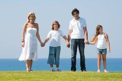 Vierköpfige Familie, die Hände anhält stockbild