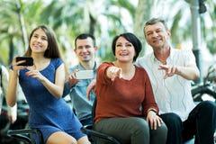 Vierköpfige Familie, die im großartigen Ausflug elektrisch sitzt stockfotografie