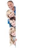 Vierköpfige Familie hinter leerem whiteboard Stockfotografie