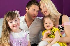 Vierköpfige Familie im purpurroten Raum Lizenzfreie Stockfotografie