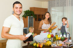 Vierköpfige Familie mit Taschen des Lebensmittels Stockfotos