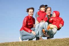 Vierköpfige Familie sitzen Stockfotos