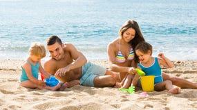 Vierköpfige Familie am Strand lizenzfreie stockfotos