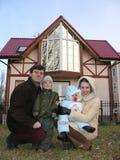 Vierköpfige Familie und Haus. 2 Lizenzfreie Stockfotos