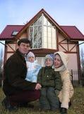 Vierköpfige Familie und Haus. Lizenzfreie Stockfotografie