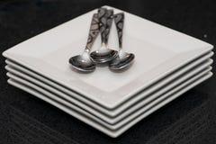 Vierkant dessertplaten en tafelzilver op banketlijst bij bedrijfs of huwelijksgebeurtenis stock afbeelding