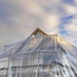 Vierkant Huis dat in aanbouw met plastiek tegen berg en bewolkte hemel wordt behandeld stock afbeeldingen