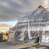 Vierkant kaderhuis dat in aanbouw met plastiek tegen berg en bewolkte hemel wordt behandeld stock foto