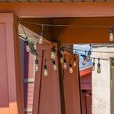 Vierkant Koord van bollen die die onder het plafond van de portiek hangen op een zonnige dag wordt bekeken stock afbeeldingen