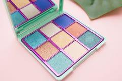 Vierkant palet van blauwe en naakte schaduwen op een roze achtergrond stock foto