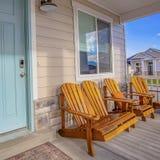 Vierkante Bruine houten stoelen voor een venster bij de zonovergoten portiek van een huis stock foto's