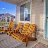 Vierkante Bruine houten stoelen voor een venster bij de zonovergoten portiek van een huis royalty-vrije stock afbeelding