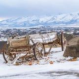 Vierkante Rustieke houten wagen naast een reusachtige rots bovenop een sneeuwheuvel in de winter stock afbeeldingen
