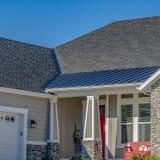 Vierkante Voorgevel van een huis met steenbakstenen muur en kleine portiek tegen blauwe hemel stock afbeeldingen