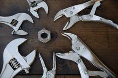 Vierkantspannschlüssel des justierbaren Schlüssels oder und Blockierungszangen auf hölzernem Hintergrund, bereiten grundlegende H Lizenzfreie Stockfotos
