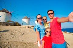Vierköpfige Familie, die selfie mit einem Stock vor Windmühlen am populären touristischen Bereich auf Mykonos-Insel, Griechenland Stockfotos