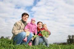 Vierköpfige Familie sitzen Lizenzfreies Stockfoto