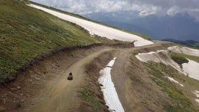 Vierlingfiets op zijn manier hoog bij de bovenkant van bergen royalty-vrije stock fotografie