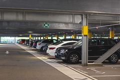 Inside of dark free multi storey car park belonging to shopping center with parked cars in Germany stock images