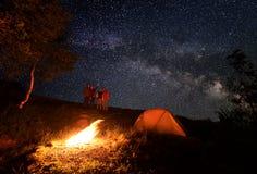 Vierpersonen genießen Sie den ungewöhnlichen Himmel, der mit hellen Sternen während des Nachtkampierens gestreut wird Stockbild