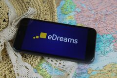 Closeup of mobile phone screen with logo lettering of online booking travel agency edreams with  sun hat and map
