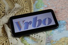 Closeup of mobile phone screen wit logo lettering of online booking travel agency vrbo with sun hat and map