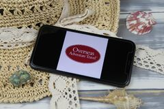 Closeup of smartphone with logo lettering of overseas adventure travel agency with sun hat and shells on wood table