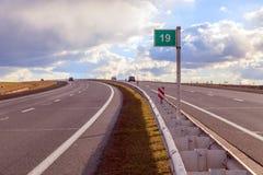 Vierspurige Autobahn mit einem Trennstreifen in der Mitte biegt nach links ab lizenzfreie stockfotos