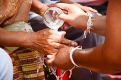 Vierta el agua en las manos de ancianos reverenciadas y pida Imagen de archivo libre de regalías