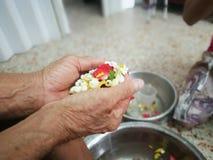 Vierta el agua en las manos de ancianos veneradas y pida bendecir fotografía de archivo libre de regalías
