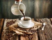 Vierta el café caliente en pequeña taza blanca fotos de archivo libres de regalías