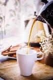 Vierta el café en una taza imagenes de archivo