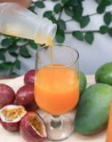Vierta el jugo, el zumo de naranja o el jugo de la pasión imagen de archivo libre de regalías