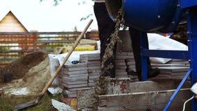 Vierta el mortero de un pequeño mezclador concreto para la construcción en un cubo Cámara lenta 1920x1080 almacen de video