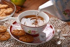 Vierta el té en la taza imagenes de archivo