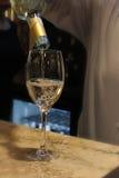 Vierta el vino blanco en el vidrio Fotografía de archivo libre de regalías