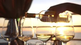Vierta el vino blanco sabroso en los vidrios de cristal con una reflexión de la puesta del sol y el mar en ellos HD, 1920x1080 Cá almacen de video