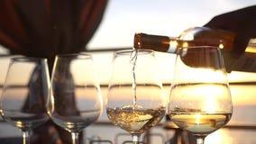 Vierta el vino blanco sobre los vidrios de cristal claros en la puesta del sol HD, 1920x1080 Cámara lenta almacen de video