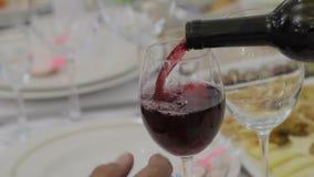 Vierta el vino en un cubilete de cristal en el banquete almacen de metraje de vídeo