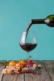 Vierta el vino rojo en un vidrio Imágenes de archivo libres de regalías