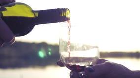Vierta el vino rojo en un vidrio vacío de una botella contra una puesta del sol en el lago Cámara lenta 1920x1080 almacen de video