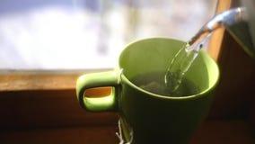 Vierta la agua caliente en una taza que se coloca cerca de la ventana, para preparar té delicioso, los remolinos del vapor, HD, 1 almacen de video
