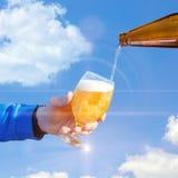Vierta la cerveza en un vidrio contra el cielo foto de archivo