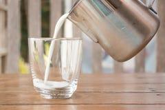 Vierta la leche de una jarra en un vidrio Fotografía de archivo libre de regalías