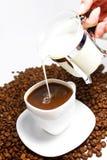 Vierta la leche en café fotos de archivo